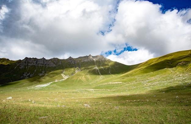 夏の山々の緑の草と青い空の風景