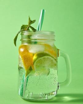 緑の壁に大きな気泡が付いた石工のガラス瓶に入った夏の自然な輝く新鮮なレモネード。冷たいアルコールまたはノンアルコールの夏の飲み物の概念。
