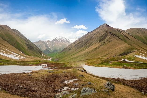 푸른 흐린 하늘을 배경으로 빙하와 눈 덮인 산봉우리가 있는 여름 자연 풍경. 조지아주 카즈베기 국립공원. 주요 백인 능선. 여행 배경입니다. 휴일, 하이킹, 스포츠, 레크리에이션.
