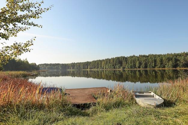Летний природный пейзаж с озером, вода, лес на горизонте неба, деревянный пирс и лодка на траве, побережье в ...