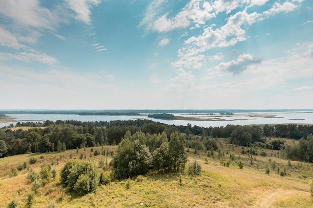 Летний природный пейзаж с небом, облаками, травой, лесными деревьями и водными озерами в нижней части сельской сцены ...