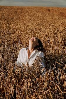 여름 자연, 여름 휴가, 휴가 및 사람들 개념. 호밀 밭의 귀에 행복 한 젊은 여자의 클로즈업