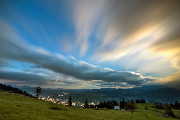 Summer night mountain panorama. green grassy mountain clearing, spruce trees on blue evening sky copy space, bright road with moving cars and dwelling lights below in valley.