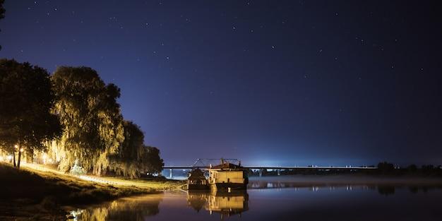 星と夏の夜空。美しい自然の背景。神秘的な風景。美しい星空。長時間露光の夜の写真のパノラマ。川の表面に映る明るい星