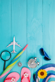 Summer objects of beautiful summer accessory on blue wooden background with copyspace