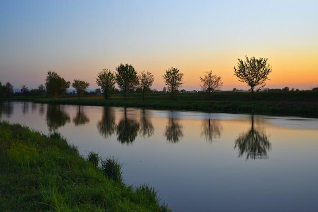 놀라운 다채로운 일몰과 함께 강에서 여름