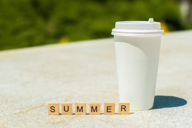 木製の立方体と白い背景の上の白いコーヒーカップの夏