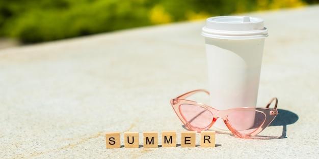 木製の立方体、ピンクのサングラス、白い背景の上の白いコーヒーカップの夏