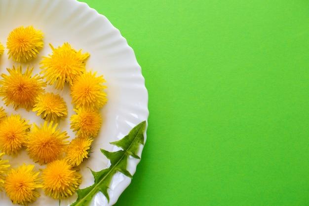 녹색 패턴에 고립 된 흰색 접시에 노란 민들레 꽃과 여름 또는 봄 배경