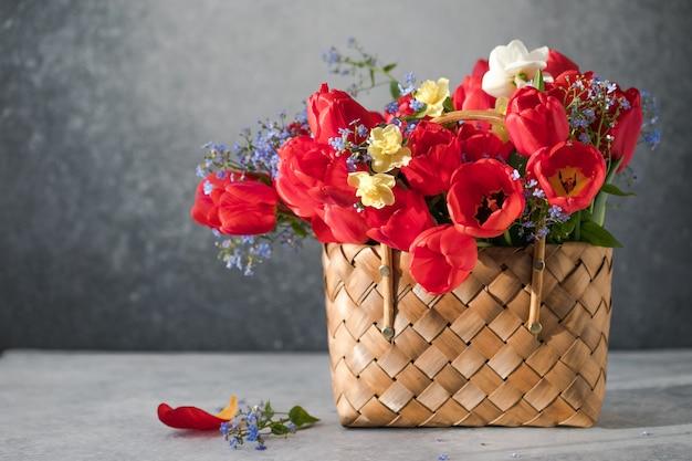 Летний или весенний букет из нарциссов и красных тюльпанов в плетеной корзине, расположенной на белой поверхности