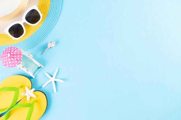夏や休暇。ビーチ帽子、サングラス、サンベッド、明るい青の背景にフリップフロップ。スペースをコピーします。