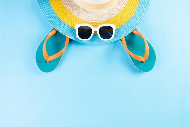 夏や休暇の概念。ビーチ帽子、サングラス、明るい青の背景にフリップフロップ。