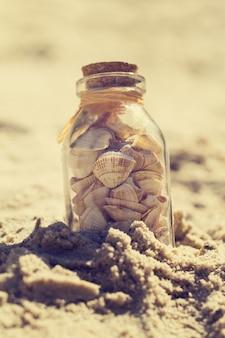 夏や休暇の概念。砂の上の瓶の中の貝殻。調色