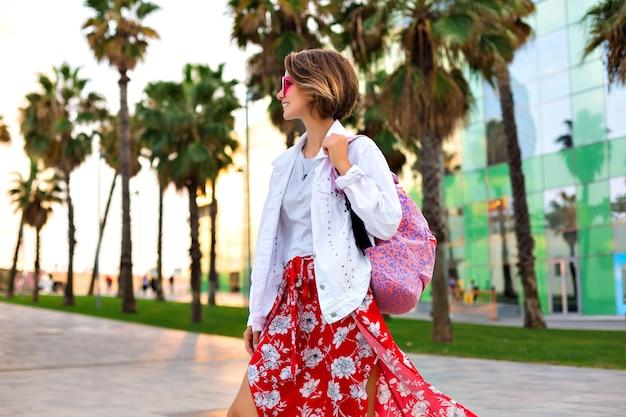 힙 스터 맥시 스커트 배낭, 화이트 데님 재킷 및 네온 선글라스를 착용하는 세련 된 유행 웃는 여자의 여름 야외 패션 밝은 초상화