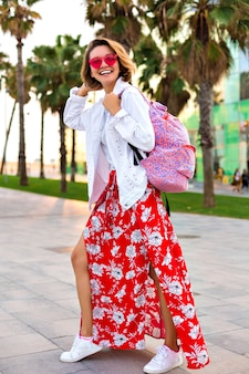 Summer outdoor fashion bright portrait of stylish trendy smiling woman wearing hipster maxi skirt backpack, white denim jacket and neon sunglasses