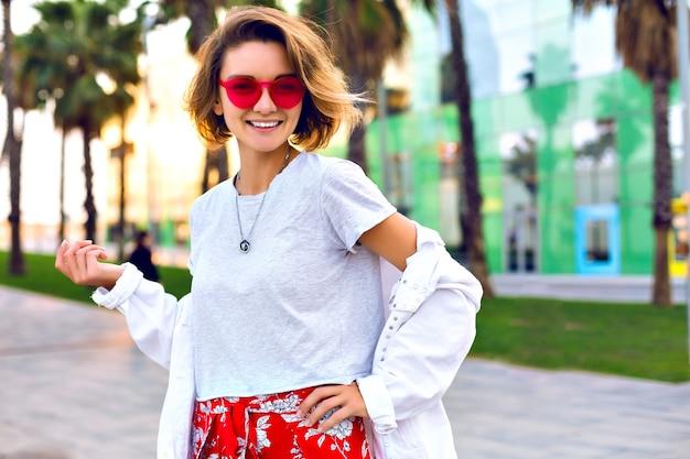 Ritratto luminoso di moda all'aperto di estate di donna sorridente alla moda elegante che indossa un abito elegante hipster, giacca di jeans bianca e occhiali da sole al neon, palme intorno, buon umore di viaggio