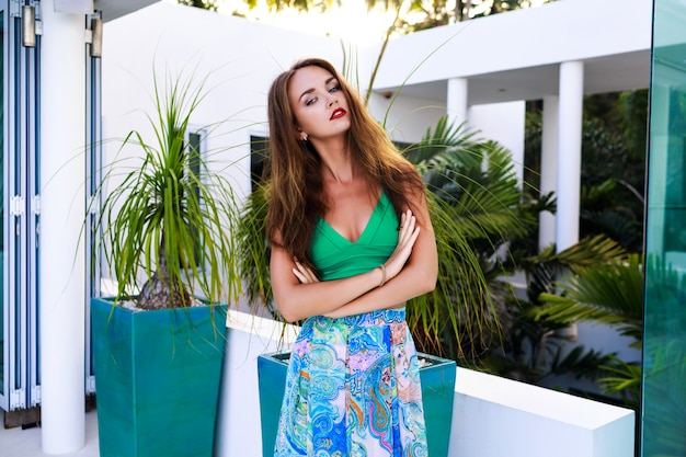 Summer outdoor fashion portrait of stunning brunette woman with long hairs and bright make up, wearing sexy silk dress, posing at luxury villa, evening sunlight