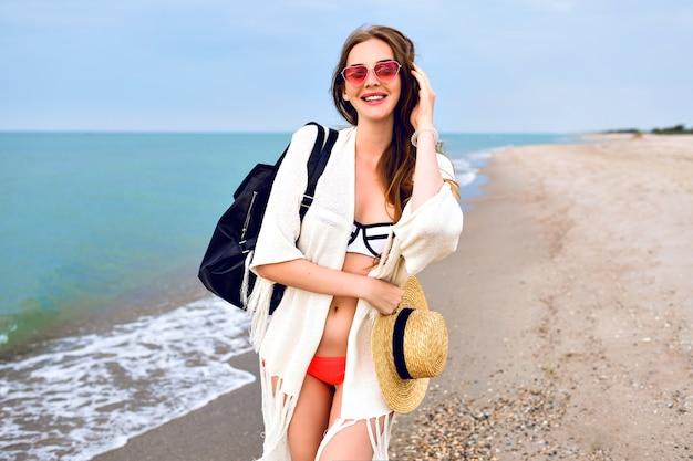 Летний открытый портрет довольно белокурой женщины в бикини, куртке в стиле бохо и солнцезащитных очках, позирует возле океана, счастливое настроение отпуска путешествия.