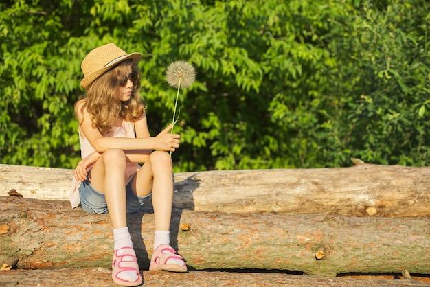大きなふわふわタンポポとロマンチックな女の子の夏の屋外のポートレート
