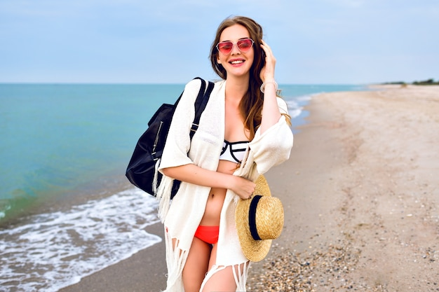 Summer outdoor portrait of pretty blonde woman wearing bikini, boho style jacket and sunglasses, posing near ocean, happy travel vacation mood.