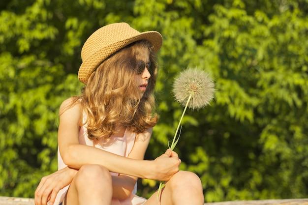 Summer outdoor portrait of romantic girl with big fluffy dandelion
