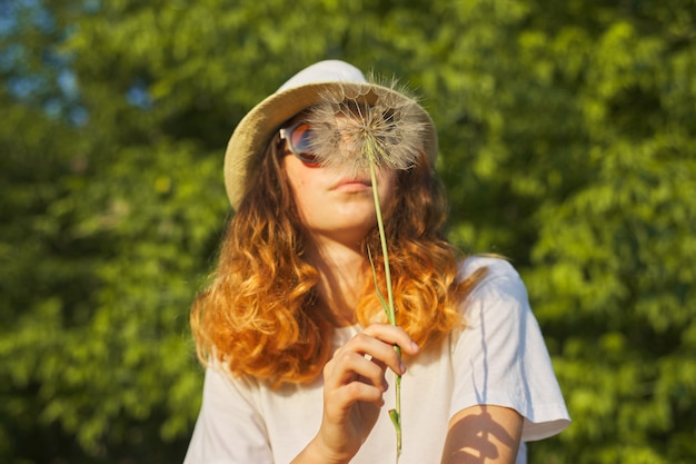 Summer outdoor portrait of romantic teenage girl in hat with big fluffy dandelion
