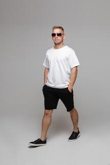 남성용 여름 복장. 선글라스, 티셔츠, 버뮤다 반바지를 입은 한 걷는 남자가 주머니에 손을 넣고 평평한 신발을 신고 걷는다. 흰 벽에 분리하십시오.