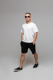 Summer outfit for men. one walking man in sunglasses, t-shirt and bermuda shorts walking in flat shoes with hands in pockets. isolate on white wall.