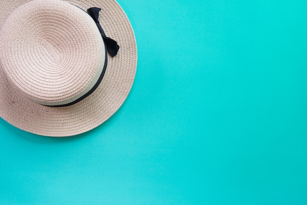 Summer panama straw hat on green pastel background.