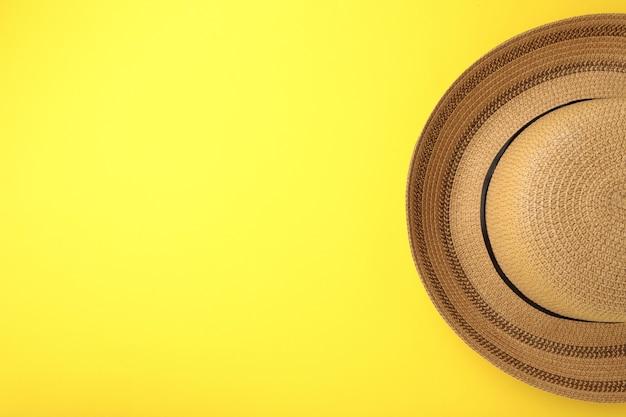 Summer panama straw hat on yellow background.