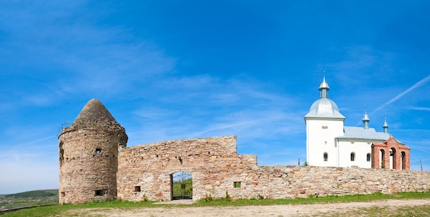 丘の頂上と背後の村(ウクライナ、テルノーピリ)にある古いキリスト教の回廊の夏のパノラマビュー。 2ショットステッチ画像。
