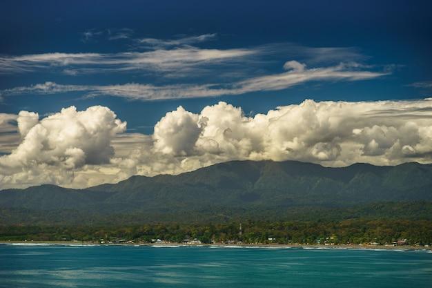 Летний панорамный вид на море и горный хребет с удивительными белыми облаками в коста-рике.