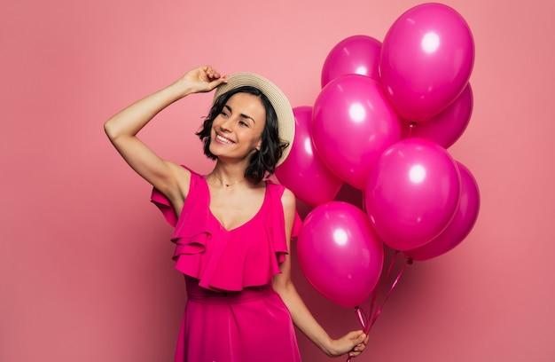 Летняя вечеринка. крупным планом фото улыбающейся девушки, которая касается своей соломенной шляпы правой рукой и держит розовые воздушные шары в левой руке, глядя в сторону.