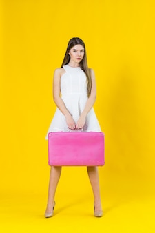 Summer photo of beautiful blonde woman with pink suitcase