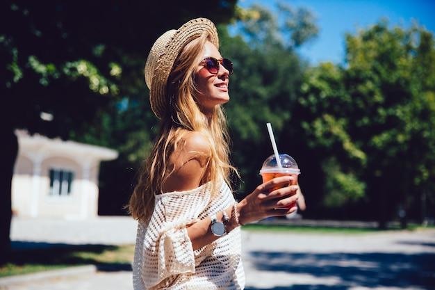 Summer photo of charming young woman in sunglasses, holds a cup of fresh cocktail