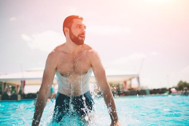 수영장에서 근육 웃는 남자의 여름 사진