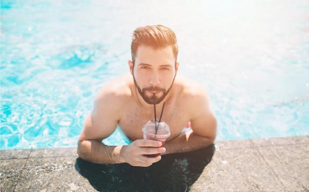 수영장에서 근육질의 웃는 남자의 여름 사진