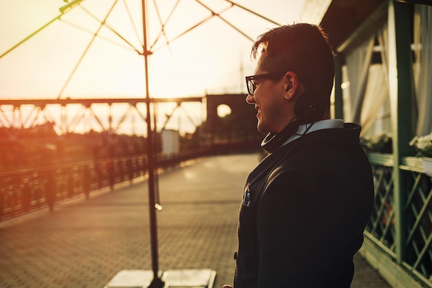 Summer photo of smiling trendy guy in glasses with headphones