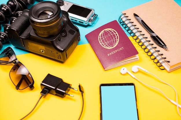Комплект летнего фотографа, который любит путешествовать на двухцветном фоне. dslr и экшн-камера рядом с другими аксессуарами, смартфоном, зарядным устройством и паспортом