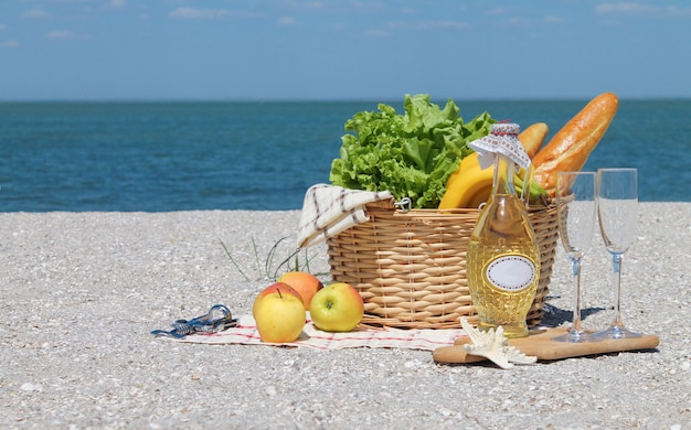 Summer picnic background with basket, wine on the beach by the ocean