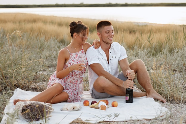 Summer picnic by the sea. couple lovers in the evening eat fruit and drink wine. romantic evening. marriage proposal