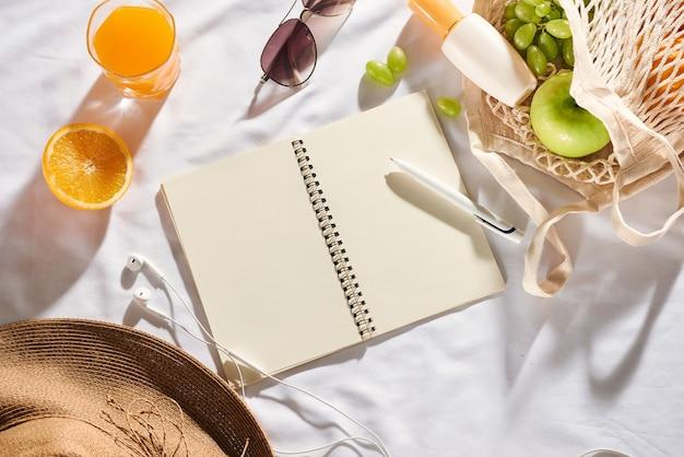 夏-ピクニックのコンセプト。ノートブック、フルーツ、バッグ、麦わら帽子、日焼け止めクリーム、カメラ、白い背景の上の日焼け止め。