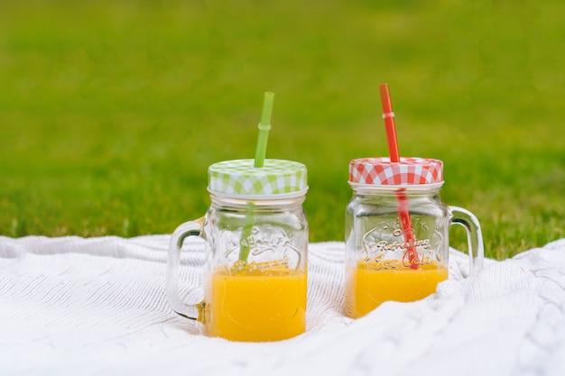 Концепция летнего пикника в солнечный день с арбузом, фруктами, букетом гортензии и подсолнухами.