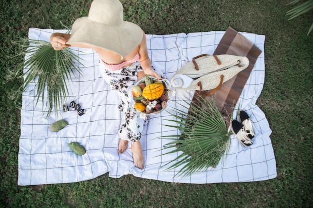 夏のピクニック、フルーツのプレートを持つ少女