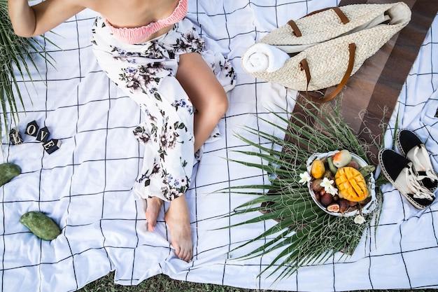 Picnic estivo, ragazza con un piatto di frutta