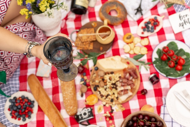 Summer picnic holidays. top view friends clink glasses on checkered blanket background. instagram content.