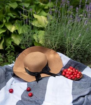 라벤더 밭에서 여름 피크닉입니다. 딸기와 밀짚 모자와 정물 여름 야외 피크닉