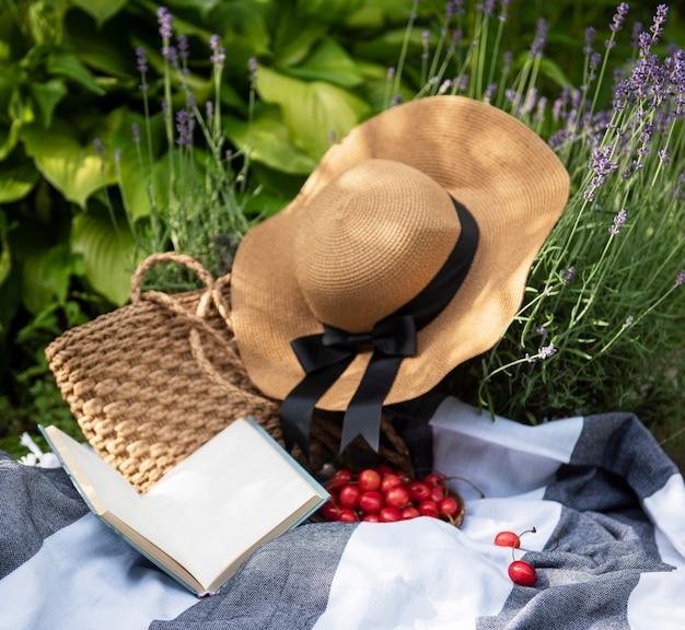 라벤더 밭에서 여름 피크닉입니다. 딸기, 밀짚 모자, 책과 함께 정물 여름 야외 피크닉