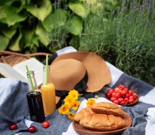 ラベンダー畑での夏のピクニック。ベリー、麦わら帽子、ジュースを使った静物夏の屋外ピクニック