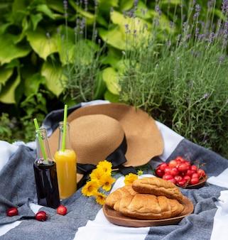 라벤더 밭에서 여름 피크닉입니다. 딸기, 밀짚 모자, 주스와 함께 정물 여름 야외 피크닉